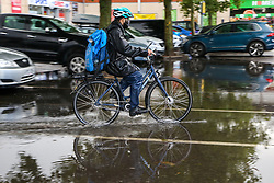 © Licensed to London News Pictures. 07/08/2021. London, UK. A cyclist rides a bike through flood water in north London. According to the Met Office, thunderstorms and heavy rain is expected in some parts of England this weekend. Photo credit: Dinendra Haria/LNP