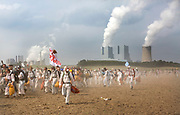 RATH, GERMANY - AUGUST 26:  Protesters cross an open field to avoid German police in the Rhineland (Rhenisch) region of mines west of Cologne on August 26, 2017 near Rath, Germany. The group was on its way to block a rail track for trains transporting coal to the RWE Power AG power plant, seen here in the background.<br />