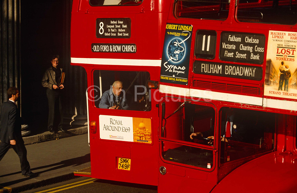In the bustle of a modern metropolis, two red Routemaster buses pass each other in Threadneedle Street. The Pillars of the Bank of England can just be seen left as pedestrians either stride past on the pavement, wait for another service or board the number 8 that is bound for Old Ford & Bow Church in the east end. Meanwhile, in the cab of his bus, the driver's hands and chest of the 11 destined for Fulham Broadway in the west can be seen in the sun, as he continues his journey in the opposite direction. Advertising is present on each mode of transport too: A travel ad for Rome (with a picture of St. Peter's in the Vatican) and for two west end musicals - Cyrano de Bergerac and Lost in Yonkers. Routemasters are largely being phased out, replaced by more modern, cleaner-engined models that hold more passengers.
