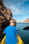 A smiling, happy woman (MR available) kayaks in Ensenada Grande, Isla Partida, La Paz, BCS, Mexico