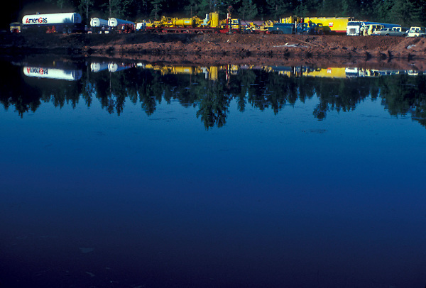 Large transport vehicles at a work site reflected in a pond