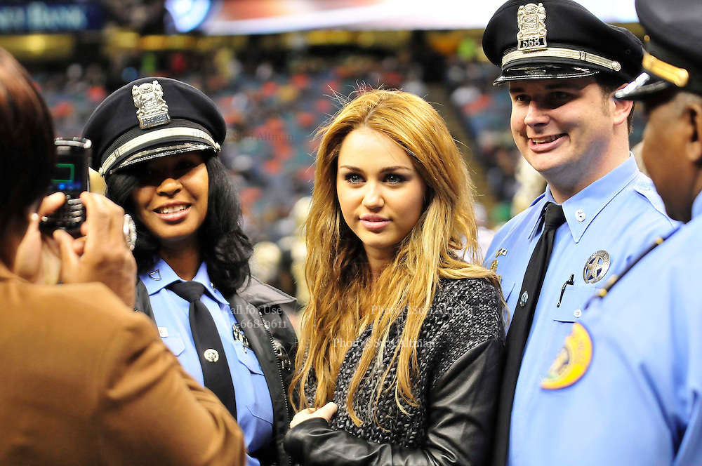 Actor and singer Miley Cyrus poses on the sidelines with the New Orleans police officers. sidelines and poses with Saints owner Rita Benson Leblanc prior to the kick off against the St. Louis Rams.The New Orleans Saints play the St. Louis Rams in New Orleans at the Super Dome Sunday Dec. 12,2010.  Saints were winning 21-6 at half time.Photo©SuziAltman.