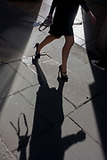 A professional-looking businesswoman walks through sunlight in a City of London street. We only see the lady's lower half, her heeled and shoes forming an exaggerated shadow on the City of London pavement, the capital's financial heart, founded in AD43.