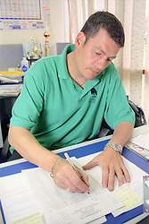Man with disability sitting at desk in office writing on form,