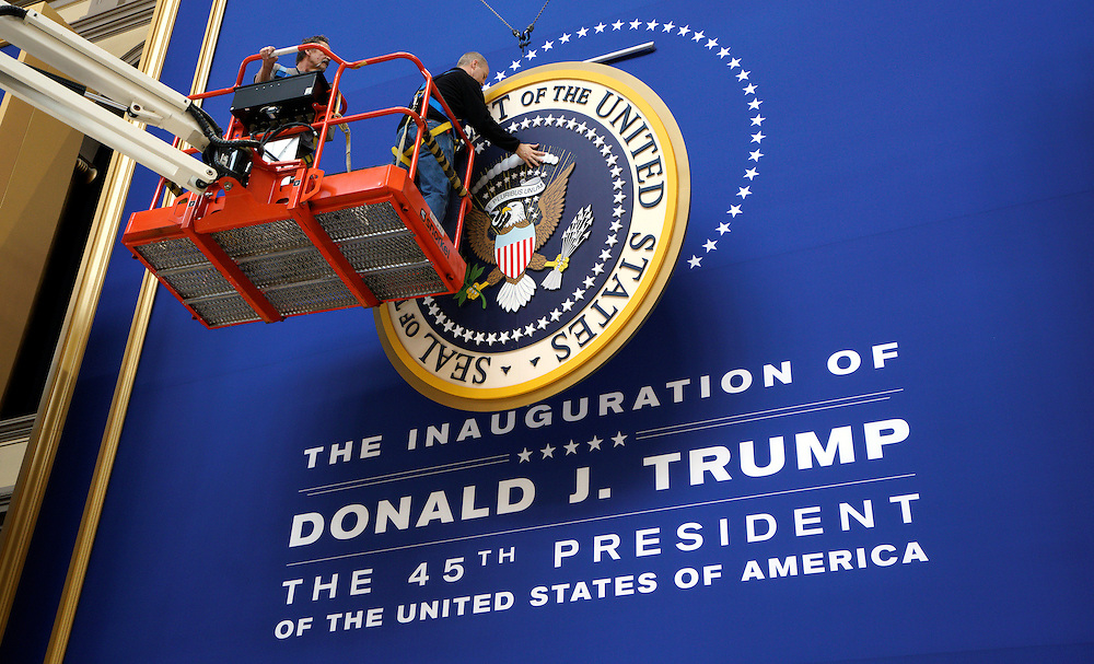 Workers install the presidential seal at the site of the Commander in Chief inaugural ball for President-elect Donald Trump in Washington, D.C. January 19, 2016.  REUTERS/Rick Wilking - RTSWDB7