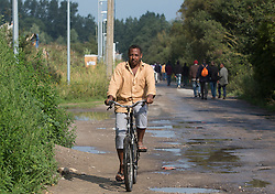 """© Licensed to London News Pictures. 30/08/2015. Calais, France. A refugee rides a bike to move around the camp, also known as the Jungle, at Calais, France. Today around a hundred British cyclists from """"Critical mass to Calais"""" arrived at the refugee camp in a two-day ride from London to donate bicycles and supplies to support the life at the site. Photo credit : Isabel Infantes/LNP"""