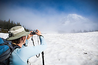 A middle aged woman taking a picture of Mount Rainier, Mount Rainier National Park, Washington, USA.