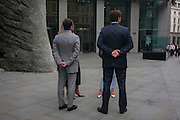 Two businessmen with female associates talk with hands behind their backs in the City of London, England UK.