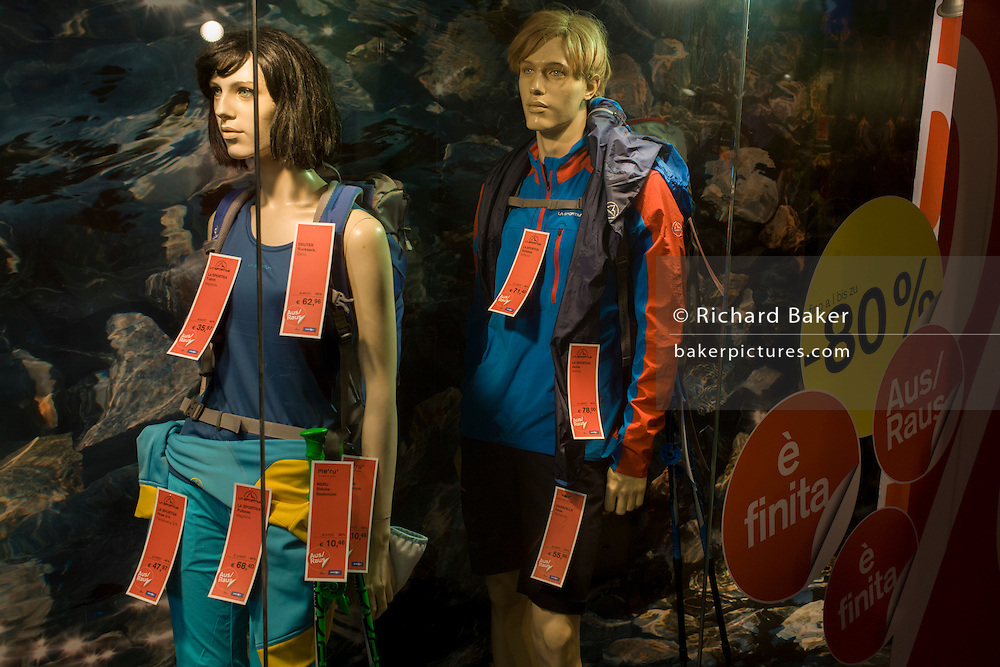 Mannequins laden with price tags in the northern Italian south Tyrolean city of Bozen-Bolzano. Hanging from the clothing on sale in this outdoor retailer in the city centre, we see discounts of up to 80% are on offer. South Tyrol is geographically the northernmost region of Italy with the best known part of South Tyrolean Alps being the Dolomites with the Schlern (2,662 mt) or the Rosengarten (3,002 mt).