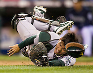 Oakland Athletics catcher makes a diving catch of a pop bunt for an out hit by Seattle Mariners' Ichiro Suzuki in Seattle. (AP Photo/John Froschauer).