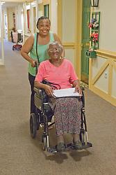 Carer pushing elderly visually impaired woman