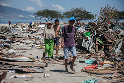 October 5, 2018 - Palu, Central Sulawesi, Indonesia - The villagers walk around the rubble near a beach Talise which was swept ashore by the tsunami, on October 5, 2018, Central Sulawesi, Indonesia. Search teams made desperate last-ditch efforts on October 5 to find survivors in destroyed buildings a week on from Indonesia's devastating quake-tsunami, have counted 1,558 dead from the double disaster on Sulawesi island, while 2,549 people are seriously injured. (Credit Image: © Ivan Damanik/ZUMA Wire)