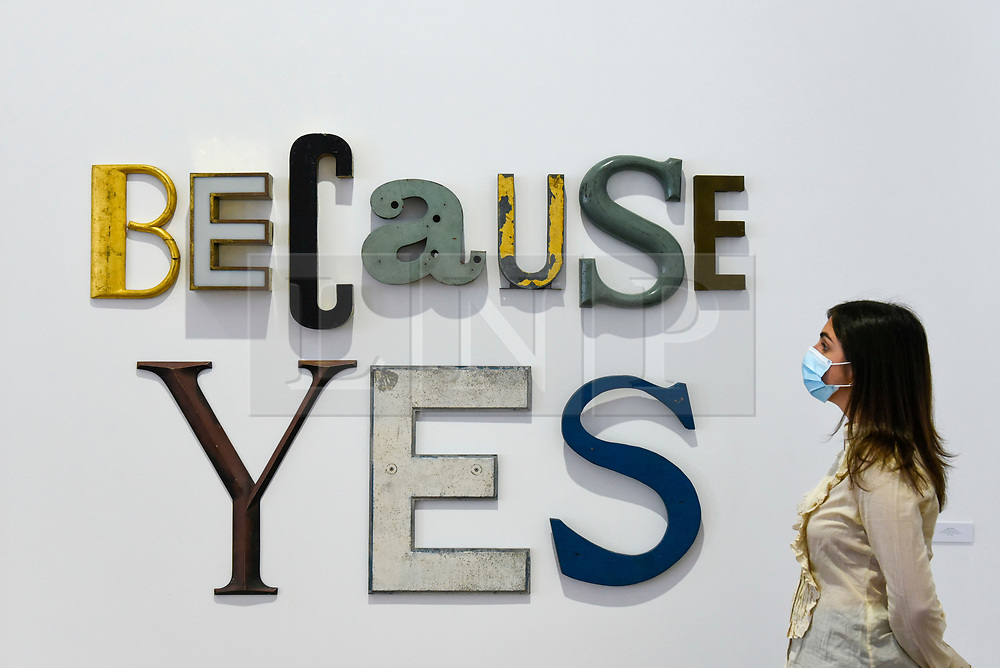 """© Licensed to London News Pictures. 16/06/2020. LONDON, UK. A staff member wearing a facemask views """"BECAUSE YES"""", 2020, by Jack Pierson on the opening day of a new exhibition """"Art Basel at Ely House"""" taking place at Galerie Thaddaeus Ropac in Mayfair.  The commercial gallery has implemented social distancing guidelines for visitors for its reopening after coronavirus pandemic lockdown restrictions were relaxed by the UK government.  The exhibition runs 16 June to 31 July 2020.  Photo credit: Stephen Chung/LNP"""