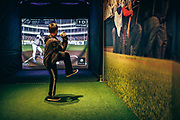 """Zachary Ennis, 9, of Chicago, takes part in the """"Batter Up"""" interactive pitching machine at the Louisville Slugger Museum. Ennis and his family were visiting Louisville Slugger and Louisville for the first time."""