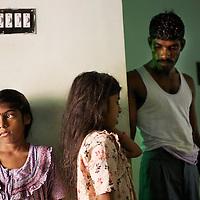 Vijyashree (left) and Vijithaa at home with their father Viswanathan.<br /><br />Vijitha and Vijyashree Viswanathan, now age 12 and 10, lost their mother and younger brother to the 2004 Asian Tsunami. The sisters continue to live with their father Viswanathan in a small house in the fishing village of Thalanguda, 5km from Cuddalore. The house does not have a toilet and water is supplied for only a short period of the day. Viswanathan married Kayalvizhi just over a year after the tsunami and the couple now have a son born in December 2006. Of the two sisters it was the elder Vijitha who initially appeared more distressed at her mother's death. But in the subsequent three years she has come to terms with her loss and seems better equipped to face the challenges of growing up without the support of her mother. In contrast Vijyashree, whos younger age may have insulated her from some of the grief experience by her sister, has fallen back in her studies becoming moody, withdrawn and reticent. Vijyashree has suffered fits for a number of years but in the past twelve months these have become more frequent. Viswanathan blames the drugs prescribed to treat his daughter's condition for her moodiness. Another explanation could be the arrival of Vijyashree's half-brother Sanjay with whom she must now compete for the affections of her father. Kayalvizhi does not appear particularly sensitive to the needs of her adopted daughters though her position cannot be easy, particularly when burdened with the task of raising a baby. Viswanathan's sister-in-law Shanthi is especially scathing of Kayalvizhi's indifference to Vijitha and Vijyashree and questions whether the girls should be expected to clean the house, clean utensils and prepare themselves for school. Shanthi complains that the girls must come to her for affection and in the case of Vijyashree this is clearly true. The fervor of Shanthi's condemnation of Kayalvizhi and, by association Viswanathan, could however be the result o