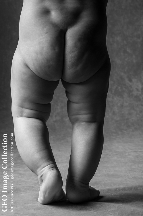 Rear view of a naked infant standing upright.