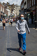 A man wearing a face covering passes through the town centre on 14th July 2021 in Windsor, United Kingdom. The UK government announced on 12th July that England will move to the final stage of easing Covid-19 restrictions on 19th July, with almost all legal restrictions on social contact removed, but they also advised the public to exercise caution given that the current wave driven by the Delta variant is not expected to peak until mid-August.