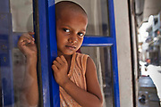 A young Indian child waits for her grandmother in the door of a health clinic in Tehkhand Slum, Delhi, India.