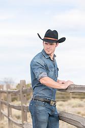sexy cowboy by a spilt rail fence on a ranch