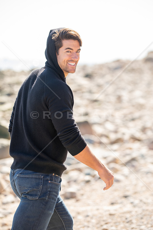 hot guy enjoying a walk at the beach