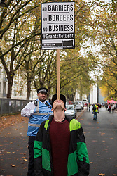 A police liaison officer watches a student balancing a placard on his forehead before the National Demonstration for a Free Education on 4th November 2015 in London, United Kingdom. The demonstration was organised by the National Campaign Against Fees and Cuts (NCAFC) in protest against tuition fees and the Government's plans to axe maintenance grants from 2016.