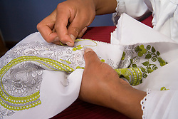 Ecuador, Zuleta, close-up of woman's hands embroidering napkin.