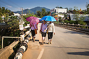 12 MARCH 2013 - ALONG HIGHWAY 13, LAOS: Women walk up Highway 13 across the Nam Kor River in Oudomaxy, Laos. The paving of Highway 13 from Vientiane to near the Chinese border has changed the way of life in rural Laos. Villagers near Luang Prabang used to have to take unreliable boats that took three hours round trip to get from the homes to the tourist center of Luang Prabang, now they take a 40 minute round trip bus ride. North of Luang Prabang, paving the highway has been an opportunity for China to use Laos as a transshipping point. Chinese merchandise now goes through Laos to Thailand where it's put on Thai trains and taken to the deep water port east of Bangkok. The Chinese have also expanded their economic empire into Laos. Chinese hotels and businesses are common in northern Laos and in some cities, like Oudomxay, are now up to 40% percent. As the roads are paved, more people move away from their traditional homes in the mountains of Laos and crowd the side of the road living off tourists' and truck drivers.    PHOTO BY JACK KURTZ
