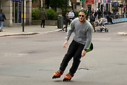 Rollerblading in the City of London on 26th May 2021 in London, United Kingdom. Man with green hair, rollerblades along Bishopsgate taking advantage of the lack of traffic during the coronavirus pandemic.