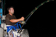 Stand up skiff angler applying lots of drag with hands and harness.