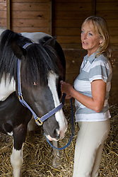 Mature woman standing next to a horse holding bridle