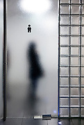 male toilette symbol with person standing behind the frosted glass door