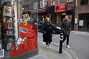 On a corner of Berwick Street in Soho at the end of the market, the shop window of Gosh Comics graphic novel and comic book store interacts with passers by in a colourful street scene on 18th February 2020 in London, England, United Kingdom. Part of Soho's ex-red light district, Berwick Street is one of central London's most varied thoroughfares full of small independent shops.