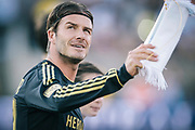 Los Angeles Galaxy midfielder David Beckham smiles as he takes the field against Real Madrid during the first half of an exhibition soccer match, Saturday, July 16, 2011, at Memorial Coliseum in Los Angeles. (AP Photo/Bret Hartman)