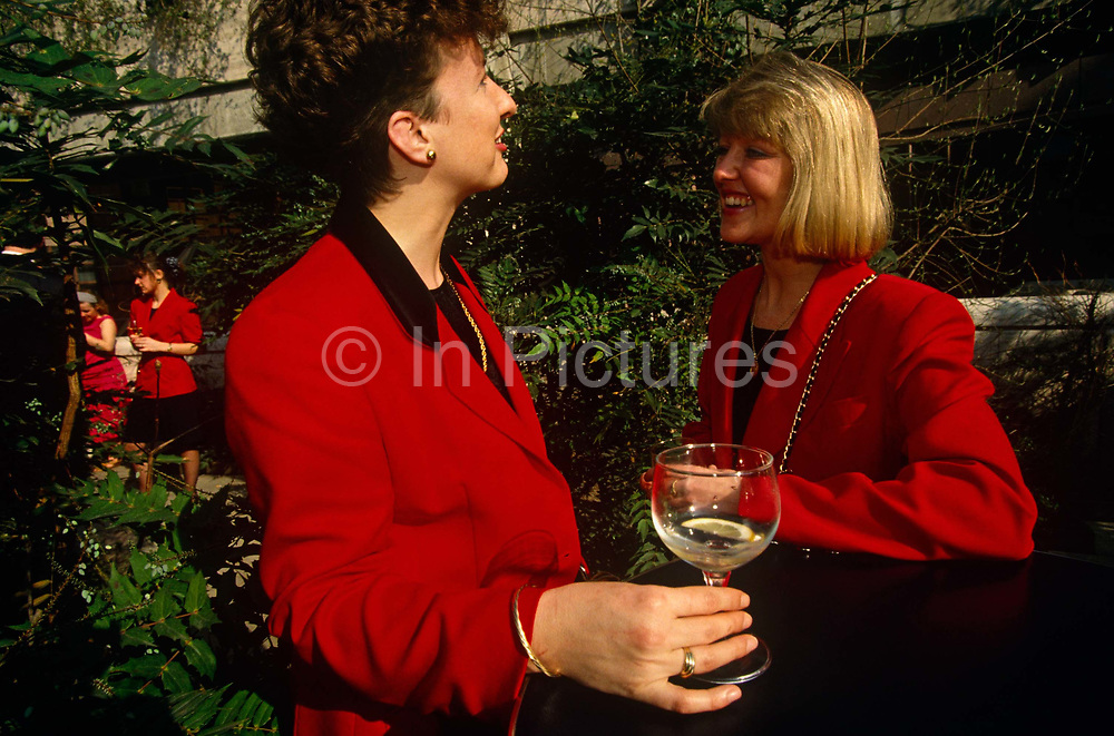 Two ladies stand outside of a bar to sip lunchtime drinks in Broadgate, City of London. Dressed in matching scarlet red jackets, the brunette and the blonde look relaxed in the warm mid-day sunshine during a warm spell in the capital. The nearest woman holds the remains of a gin and tonic whose lemon slice  is at the bottom of her glass while her friend or colleague, with wide shoulder pads and gold chain strap for her bag draped over across a shoulder, smiles to show white teeth. In the background are other women who wear the same red clothes and these primary colours are set amongst the deep green foliage of the bar's plants.