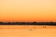 People on canoes and river at sunset, Zambezi River, Zambia