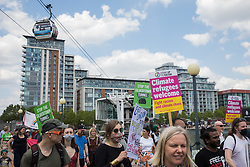 London, UK. 5th June, 2021. Environmental activists and local residents pass beneath the Emirates Air Line cable car as they protest against the construction of the Silvertown Tunnel. Campaigners opposed to the controversial new £2bn road link across the River Thames from the Tidal Basin Roundabout in Silvertown to Greenwich Peninsula argue that it is incompatible with the UK's climate change commitments because it will attract more traffic and so also increased congestion and air pollution to the most polluted borough of London.