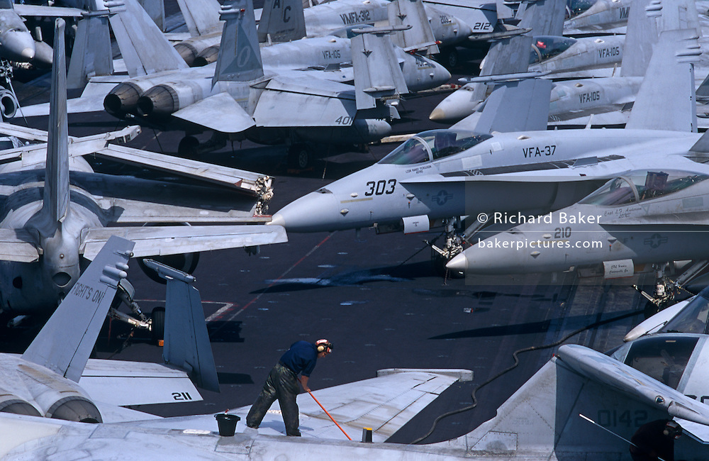 Up on the top deck, we see a lone sailor brushing off the grubby surfaces of parked F/A-18C Hornets and S-3 Vikings on the US Navy aircraft carrier USS Harry S Truman during its deployment patrol of the no-fly zone at an unknown location in the Persian Gulf. Stacked together in tight formation to fit them all together during a daytime break in operations, the man bends into his task during the hottest time of day. The Truman is the largest and newest of the US Navy's fleet of new generation carriers, a 97,000 ton floating city with a crew of 5,137, 650 are women. The Iraqi no-fly zones (NFZs) were proclaimed by the United States, United Kingdom and France after the Gulf War of 1991 to protect humanitarian operations in northern Iraq and Shiite Muslims in the .