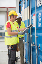 Construction workers with storage checklist and digital tablet at site, Munich, Bavaria, Germany, Europe