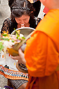 "15 JULY 2011 - PHRA PHUTTHABAT, SARABURI, THAILAND:   A woman makes an offering to a monk during the Tak Bat Dok Mai at Wat Phra Phutthabat in Saraburi province of Thailand, Friday, July 15. Wat Phra Phutthabat in Phra Phutthabat, Saraburi, Thailand, is famous for the way it marks the beginning of Vassa, the three-month annual retreat observed by Theravada monks and nuns. The temple is highly revered in Thailand because it houses a footstep of the Buddha. On the first day of Vassa (or Buddhist Lent) people come to the temple to ""make merit"" and present the monks there with dancing lady ginger flowers, which only bloom in the weeks leading up Vassa. They also present monks with candles and wash their feet. During Vassa, monks and nuns remain inside monasteries and temple grounds, devoting their time to intensive meditation and study. Laypeople support the monastic sangha by bringing food, candles and other offerings to temples. Laypeople also often observe Vassa by giving up something, such as smoking or eating meat. For this reason, westerners sometimes call Vassa the ""Buddhist Lent."" The tradition of Vassa began during the life of the Buddha. Most of the time, the first Buddhist monks who followed the Buddha did not stay in one place, but walked from village to village to teach. They begged for their food and often slept outdoors, sheltered only by trees. But during India's summer rainy season living as homeless ascetics became difficult. So, groups of monks would find a place to stay together until the rain stopped, forming a temporary community. Wealthy laypeople sometimes sheltered monks on their estates. Eventually a few of these patrons built permanent houses for monks, which amounted to an early form of monastery.    PHOTO BY JACK KURTZ"