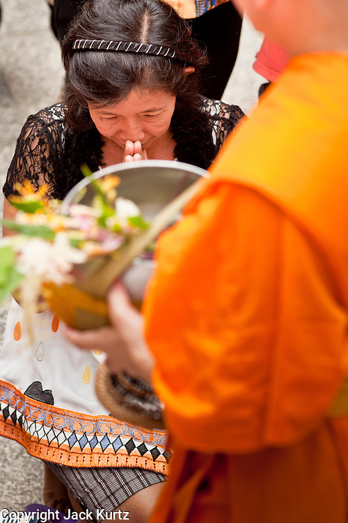 """15 JULY 2011 - PHRA PHUTTHABAT, SARABURI, THAILAND:   A woman makes an offering to a monk during the Tak Bat Dok Mai at Wat Phra Phutthabat in Saraburi province of Thailand, Friday, July 15. Wat Phra Phutthabat in Phra Phutthabat, Saraburi, Thailand, is famous for the way it marks the beginning of Vassa, the three-month annual retreat observed by Theravada monks and nuns. The temple is highly revered in Thailand because it houses a footstep of the Buddha. On the first day of Vassa (or Buddhist Lent) people come to the temple to """"make merit"""" and present the monks there with dancing lady ginger flowers, which only bloom in the weeks leading up Vassa. They also present monks with candles and wash their feet. During Vassa, monks and nuns remain inside monasteries and temple grounds, devoting their time to intensive meditation and study. Laypeople support the monastic sangha by bringing food, candles and other offerings to temples. Laypeople also often observe Vassa by giving up something, such as smoking or eating meat. For this reason, westerners sometimes call Vassa the """"Buddhist Lent."""" The tradition of Vassa began during the life of the Buddha. Most of the time, the first Buddhist monks who followed the Buddha did not stay in one place, but walked from village to village to teach. They begged for their food and often slept outdoors, sheltered only by trees. But during India's summer rainy season living as homeless ascetics became difficult. So, groups of monks would find a place to stay together until the rain stopped, forming a temporary community. Wealthy laypeople sometimes sheltered monks on their estates. Eventually a few of these patrons built permanent houses for monks, which amounted to an early form of monastery.    PHOTO BY JACK KURTZ"""
