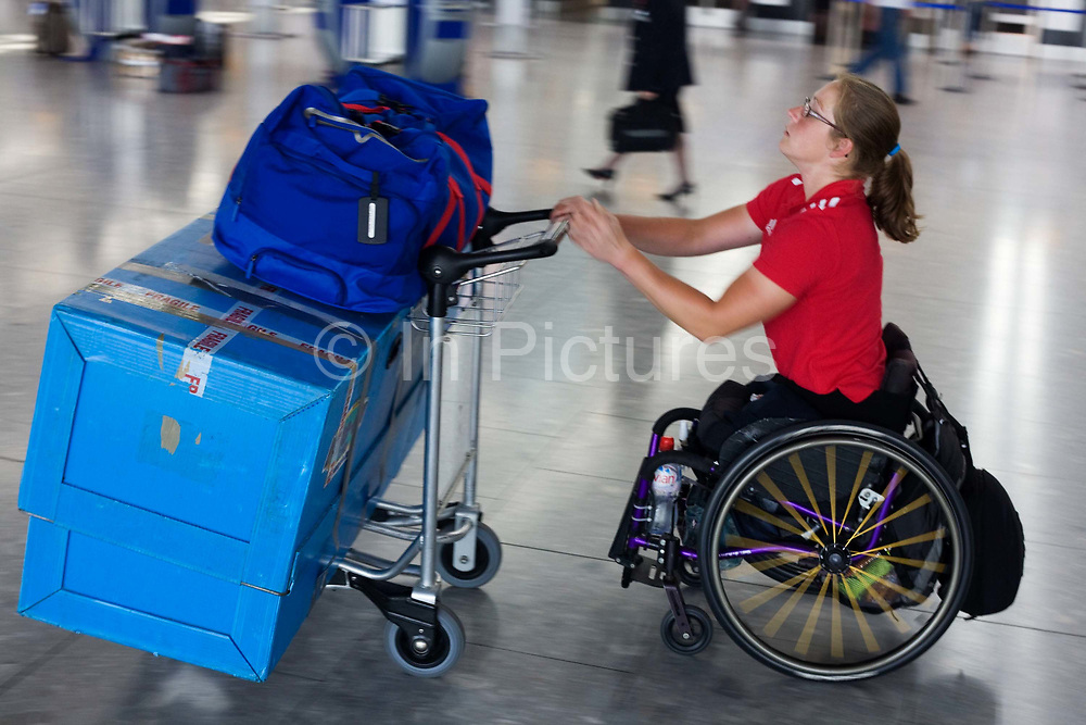 """A disabled airline passenger makes her own way through the Departures concourse of Heathrow Airport's Terminal 5. Pushing her racing wheelchair, possibly for a race in another country, the lady heads for a British Airways check-in zone before a long-haul flight to compete as a paraplegic. Pushing her possessions on an airport trolley, she speeds through the terminal showing tanned, muscular arms and a bottle of Evian mineral water. From writer Alain de Botton's book project """"A Week at the Airport: A Heathrow Diary"""" (2009)."""