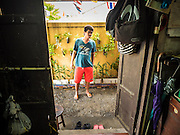14 SEPTEMBER 2015 - BANGKOK, THAILAND:  A neighbor looks into a home that is being vacated near Wat Kalayanamit. Fiftyfour homes around Wat Kalayanamit, a historic Buddhist temple on the Chao Phraya River in the Thonburi section of Bangkok are being razed and the residents evicted to make way for new development at the temple. The abbot of the temple said he was evicting the residents, who have lived on the temple grounds for generations, because their homes are unsafe and because he wants to improve the temple grounds. The evictions are a part of a Bangkok trend, especially along the Chao Phraya River and BTS light rail lines. Low income people are being evicted from their long time homes to make way for urban renewal.           PHOTO BY JACK KURTZ