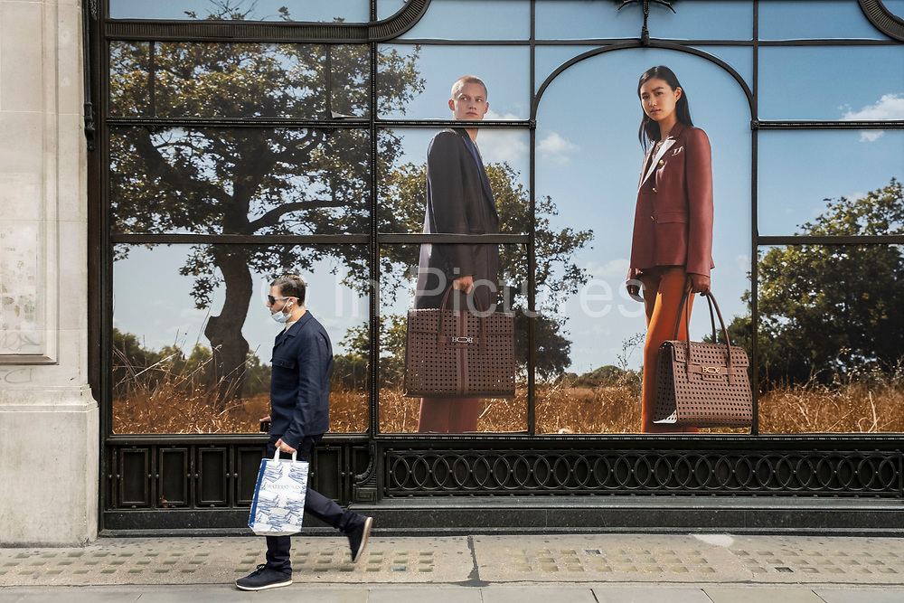 Large scale luxury brand advertising images in shop windows along Regent Street on 26th May 2021 in London, United Kingdom. Passing people interact with the huge figures in these photographs as if tiny in comparison. This area of the capital is known for its exclusive shops whose vrands are aimed at the rich and wealthy.