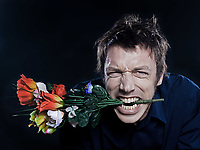 studio portrait on black background of a funny expressive caucasian man offering flowers anger