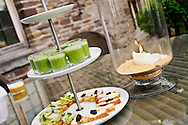 Appetizers of soda-bread canapes with pesto and hummus with sun-dried tomatoes and fresh pea soup are served alfresco on a terrace.