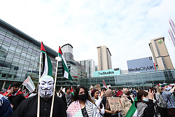 © Licensed to London News Pictures. 29/05/2021. Salford, UK.  A masked protester at a 'Protest for Palestine' outside the BBC studios in Media City. Pro-Palestine demonstrations have been taking place worldwide in the wake of Israel's 11 day bombardment of Gaza which resulted in hundreds of civilian deaths. Photo credit: Adam Vaughan/LNP