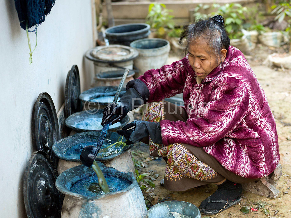 Pheng prepares an indigo dye bath in traditional ceramic pots for dyeing cotton fabric in the Tai Lue village of Ban Viengkao, Sayaboury province, Lao PDR. Indigo dye is made from the fresh leaves and stem of the indigo plant which are fermented and then mixed with limestone to turn it the distinctive blue colour. One of the most ethnically diverse countries in Southeast Asia, Laos has 49 officially recognised ethnic groups although there are many more self-identified and sub groups. These groups are distinguished by their own customs, beliefs and rituals.