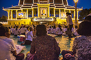 """29 JANUARY 2013 - PHNOM PENH, CAMBODIA:   People gather on the plaza in front of the Royal Palace in Phnom Penh, Cambodia, to mourn for late Cambodian King Norodom Sihanouk. Sihanouk (31 October 1922- 15 October 2012) was the King of Cambodia from 1941 to 1955 and again from 1993 to 2004. He was the effective ruler of Cambodia from 1953 to 1970. After his second abdication in 2004, he was given the honorific of """"The King-Father of Cambodia."""" Sihanouk held so many positions since 1941 that the Guinness Book of World Records identifies him as the politician who has served the world's greatest variety of political offices. These included two terms as king, two as sovereign prince, one as president, two as prime minister, as well as numerous positions as leader of various governments-in-exile. He served as puppet head of state for the Khmer Rouge government in 1975-1976. Most of these positions were only honorific, including the last position as constitutional king of Cambodia. Sihanouk's actual period of effective rule over Cambodia was from 9 November 1953, when Cambodia gained its independence from France, until 18 March 1970, when General Lon Nol and the National Assembly deposed him. Upon his final abdication, the Cambodian throne council appointed Norodom Sihamoni, one of Sihanouk's sons, as the new king. Sihanouk died in Beijing, China, where he was receiving medical care, on Oct. 15, 2012. His cremation is scheduled to take place on Feb. 4, 2013. Over a million people are expected to attend the service.     PHOTO BY JACK KURTZ"""