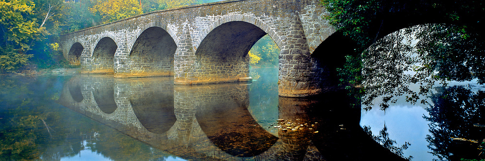 Mist over still water further enhances the lovely reflection of the stone curves of Wilson Bridge, at Hagerstown in Maryland.