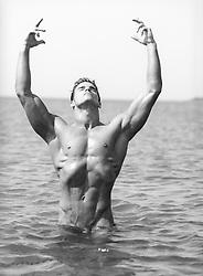 naked bodybuilder posing in the ocean